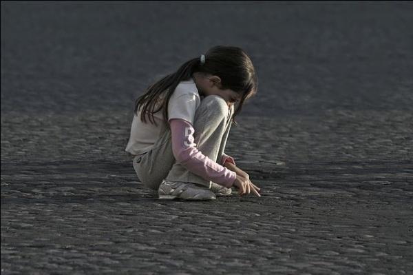 enfant fille seule recroquevillée sur la plage